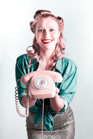 saleslady: Beautiful Smiling Pinup Woman Holding Retro Turn Dial Phone In A Contact Us Concept Stock Photo