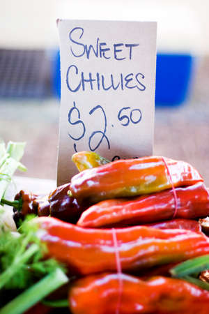 organic peppers sign: Market Stall Sign Selling Sweet Chillies For $2.50 A Bunch Stock Photo