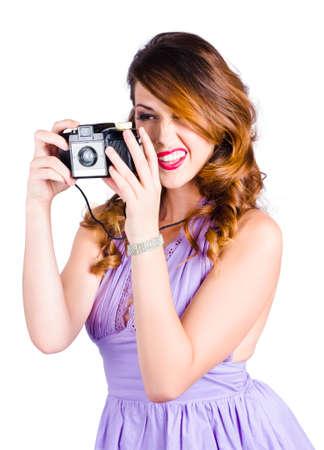 AFICIONADOS: Atractiva fotógrafa amateur en práctica el vestido cuando se toma una fotografía de la película con la cámara retro, fondo blanco Foto de archivo