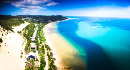 Moreton Island, Queensland, Australia, picturesque view along the coastline of a row of cottages facing the blue ocean and beach, tropical island holiday concept