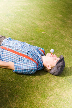 tee off: Wacky Concept Of A Golfing Man Laying Down On A Golf Course Holding A Golf Tee And Ball In His Mouth Ready For The Tee Off