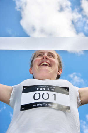 exhilarated: Fun Run Competitor Runs Across The Finish Line With Arms Open And Victorious Expression Across Her Face