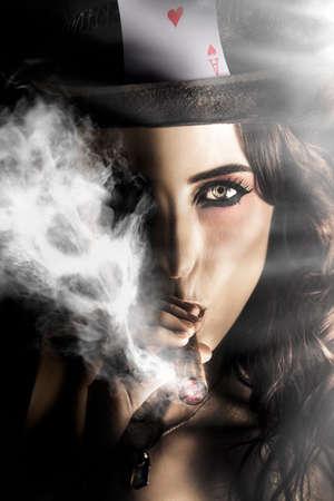 persona fumando: La hembra atractiva de la tarjeta del jugador fumadores Hasta el éxito, mientras que ganan dinero con una cara de póquer Foto de archivo