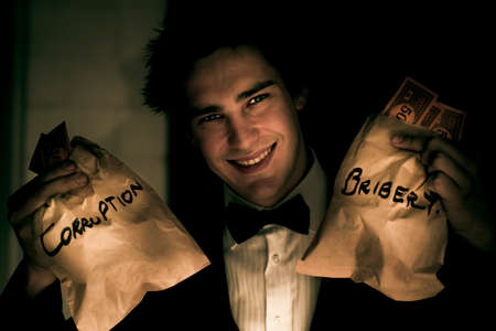 conman: Bribery And Corruption Scam Sees A Dodgy Business Con Man Holding Up Two Brown Paper Bags Full Of Money In The Dark Alleyway Of Fraudulent Dishonesty Stock Photo
