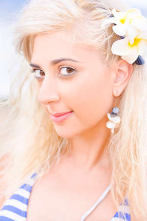 blemish: Fresh Clear And Blemish Free Beauty And Skincare Concept Amid A Pretty Beautiful Blonde Woman Smiling With A Yellow Frangipani Flower In Her Hair