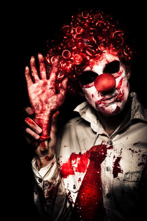 hand: Horror Clown Waving Chopped Off Hand To Welcome You To A Evil Circus Act Of Terror On Black Background Stock Photo