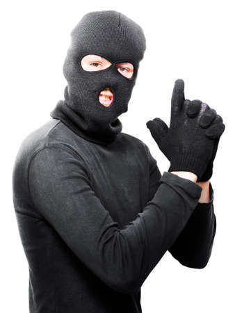 armed robbery: Male criminal in mask making a hand gun gesture in a depiction of a armed holdup or robbery isolated on white background