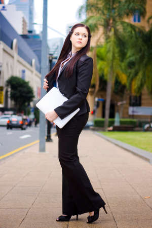 woman business suit: Online Business Mobility Concept With A Full Body Portrait Of A Young Business Woman In Black Suit On The Move Around Town With A Laptop In Hand