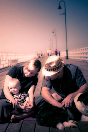 baby sit: Vacationing young couple with their baby boy take a break during a busy day sightseeing to sit and rest on the boardwalk