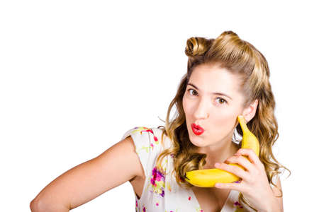 hilarious: Funny healthy eating pin-up woman with nineteen-fifties hairstyle talking on banana phone with hilarious expression when ordering organic fresh fruit on white background Stock Photo