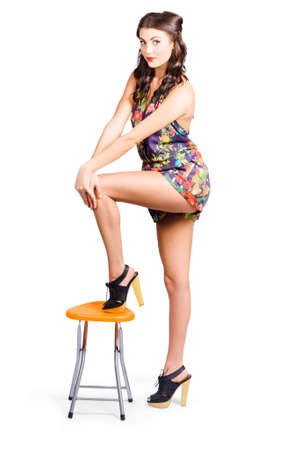 sexy fashion: Sexy pin-up model with long silky legs posing on orange stool in stylish retro fashion. Footwear concept