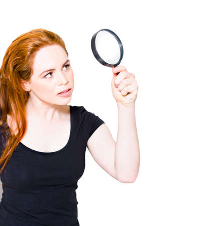 detects: Isolated Studio Portrait Of A Beautiful Female Detective With Red Hair Searching And Analyzing A Crime Scene For Clues When Holding A Private Eye Magnifying Glass