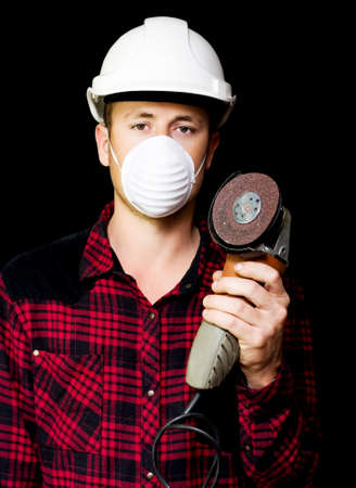 sander: Young metal fabrication workman in a hardhat and mask holding up a small handheld rotary disc sander on a black studio background