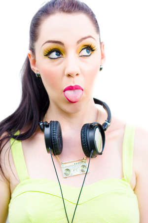 sticking: Mad About Music Is A Cheeky Woman In Fluro 80s Clothing Wearing Retro Headphones And Poking Tongue Out Of Mouth, Studio Image Isolated On White Background Stock Photo