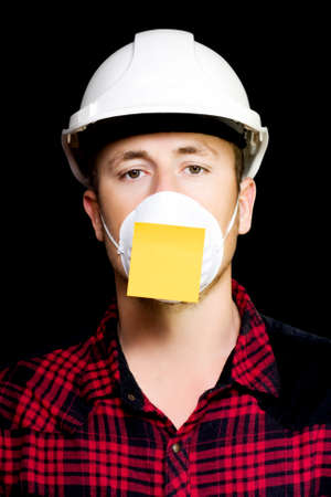 forgetful: Forgetful young workman wearing a protective helmet and safety mask with a blank sticky note reminder on black background Stock Photo