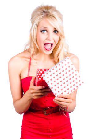 gasping: Woman gasping with excitement while holding a valentines day gift box. Over white background.