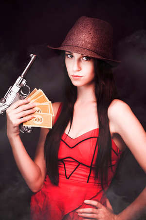 takings: Sexy but sinister female gangster wearing a hat and red dress displaying her gun and ill gotten loot Stock Photo