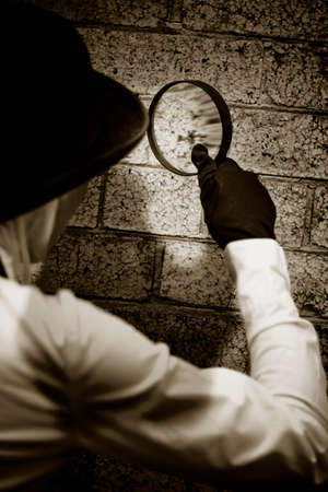 clues: Retro Private Eye Detective Searching For Clues By Investigating A Suspected Crime Scene Wall With A Magnifying - Looking Glass