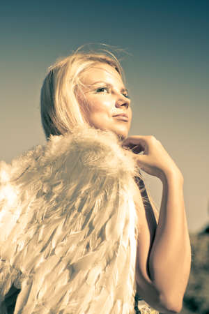 angel wing: Golden Female Angel Wearing White Feather Wings While Looking To The Heavens Above In A Depiction Of Faith And Belief