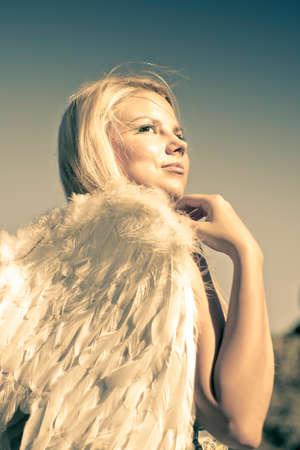 angel de la guarda: Ángel de oro femenino vestido de blanco de la pluma de las alas mientras mira a los cielos arriba en una representación de fe y creencia Foto de archivo