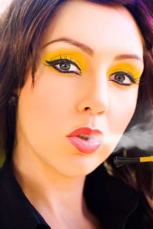 puffing: Face Of A Gorgeous And Stunning Young Brunette Woman In Retro Summer Makeup Blowing And Puffing Out Cigarette Smoke In A Glamour Smoking Style Portrait