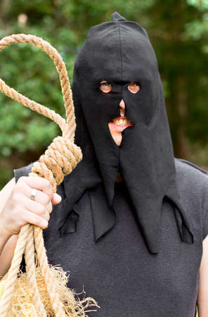 deranged: Black Hooded Medieval Hangman Stands With An Look Of Anger And Hatred With Rope Noose At Outdoor Gallows Stock Photo