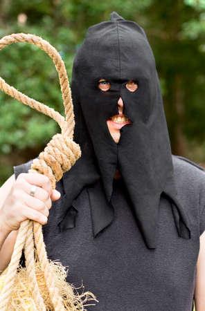 ahorcado: Negro con capucha medieval verdugo coloca con una mirada de ira y odio Con Soga Cuerda En Cadalso exterior