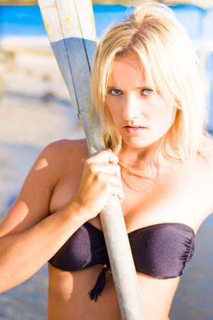 indignant: Athletic And Healthy Blonde Bikini Girl With Glamorous And Dramatic Expression Posing With Two Wooden Oars At The Beach In Front Of Ocean Background