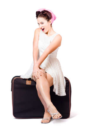 fifties: Female pinup travelling tourist sitting on luggage in fifties fashion style over white background