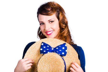 broadly: Pinup girl smiling broadly holding straw hat tied with blue ribbon and bow on white background