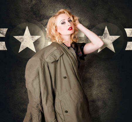 provoking: Old fashion fine art portrait of a blond military pinup girl wearing vintage model makeup and 60s hair style provoking a sensual look in retro army clothes. Historic armed forces background