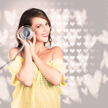 tin can phone: Smiling woman listening to a tin can phone on grey heart shaped background