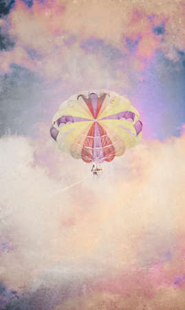 olden day: Vintage Parachute In Clouds. Faded distressed and textured vintage image of a parachute in the distant beautiful pastel toned clouds.
