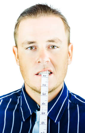 unemotional: Man biting and holding tape measure in mouth on white background