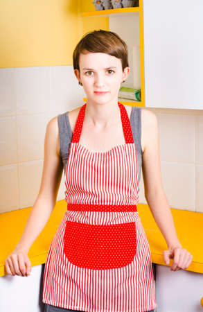 young wife: Portrait of a young house wife wearing red striped bib on kitchen background