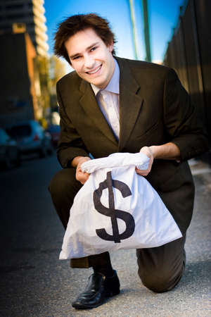 finders: Happy Business Man Smiling While Kneeling Down On The City Street Holding A Large Sum Of Cash In A Dollar Sign Money Bag In A Sign Of Business Earnings