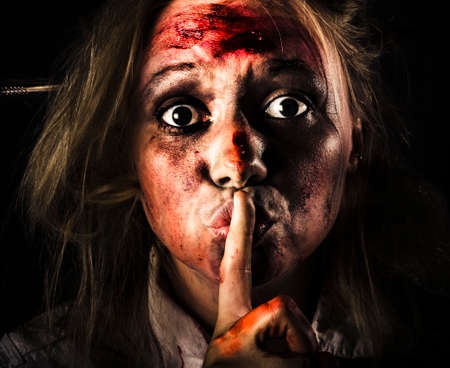 stranger: Close-up halloween portrait of a scary zombie horror face gesturing silence at the dead of night with bloody terror Stock Photo