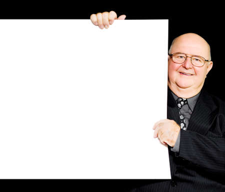 annoucement: Happy jolly retired gentleman holding the side of a blank white sign or placard to advertise senior retirement and savings plans and offering his support and endorsement