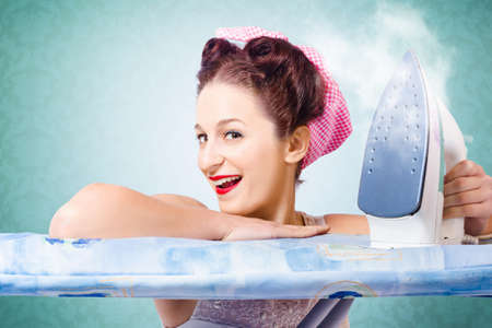housecleaning: Funny pin-up cleaning woman having fun during spring clean wearing pink head scarf and red lips make-up holding steaming hot clothing iron inside home interior