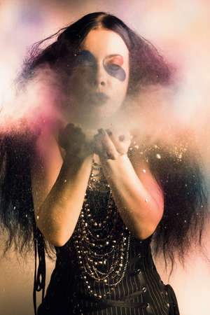 enchanting: Enchanting mystic sorcerer woman creating spells of colorful magic when blowing a cloud of dream potion into the air of a fantasy realm Stock Photo