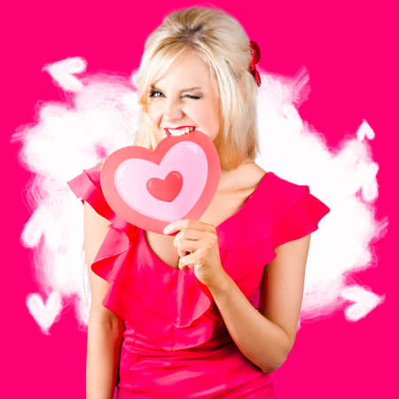 tantalising: Adorable blond girl winking while biting into a valentine heart. Eat your heart out concept Stock Photo