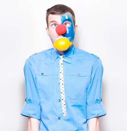 gente loca: Mirada divertido payaso intentar tragar Un limón entero con una expresión agria en una representación de acidez e indigestión