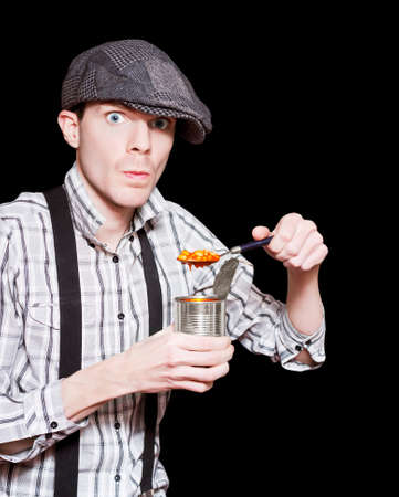 waif: Vintage Street Peasant Boy In Flat Cap Eating Baked Beans From A Can In A Depiction Of The Great Depression