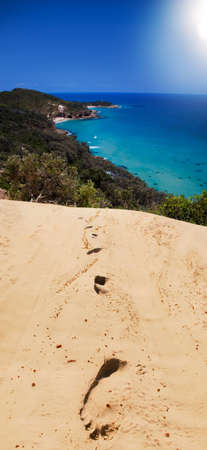 holidaying: Footsteps Leading From A Beach Getaway Retreat Stock Photo