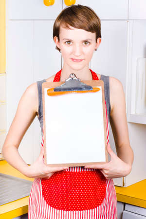 pinafore: Attractive woman wearing red pinafore standing in the kitchen holding a blank recipe board Stock Photo