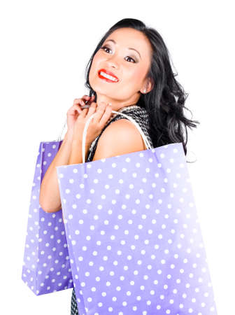 spendthrift: Isolated portrait of a young chinese woman walking with polka dot shopping bags