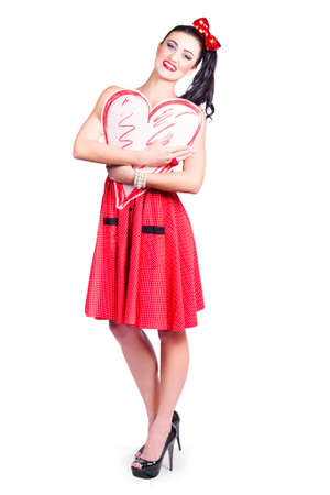 anniversary sexy: Beautiful young woman holding heart shape with her hands over white background