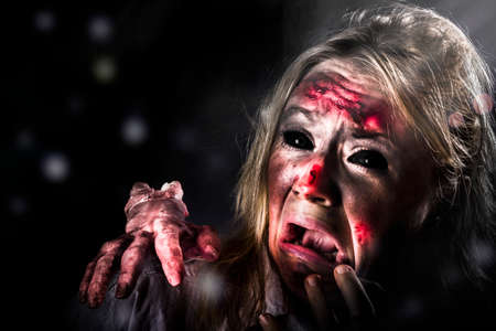 'young things': Scary halloween horror. Zombie in pitch black forest expressing fear when getting attacked from evil thing