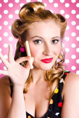 charisma: Cute amercian pinup girl with classic bright makeup and1950 hair curles holding laundry peg. Pink polka dot background