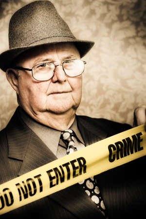 observant: Vintage portrait of an elderly perceptive crime detective with an observant look in his eye watching carefully as he stands behind the tape at a crime scene
